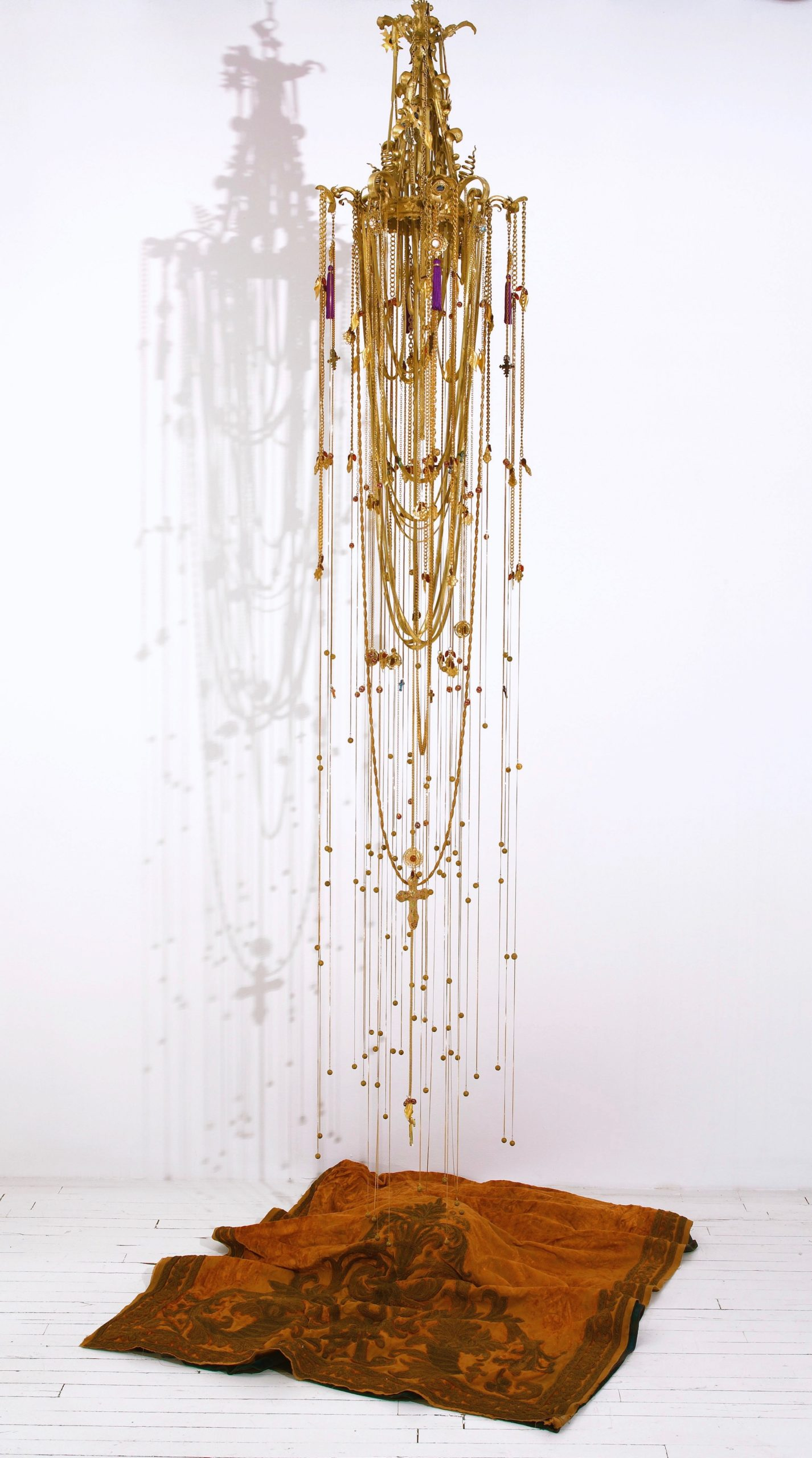 Esperanza Cortés; EMPIRE; 2016; Chandelier, gold leaf, 1000 feet of gold plated jewelry chain, gold plated metal leaves, brass beads, glass beads; 18' L x 6' Diameter. The history of colonial empire is the history of the Americas, specially places like my birthplace Colombia.